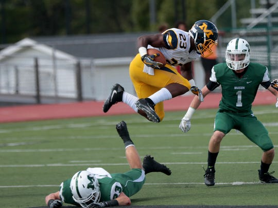 Moeller's Colin Thurman (23) hurdles Mason's   Cole Pearce during their football game against  Sunday, Sept. 11, 2016.