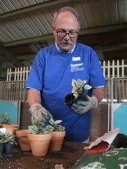 Dennie Striker of Richland Bank pots flowers during