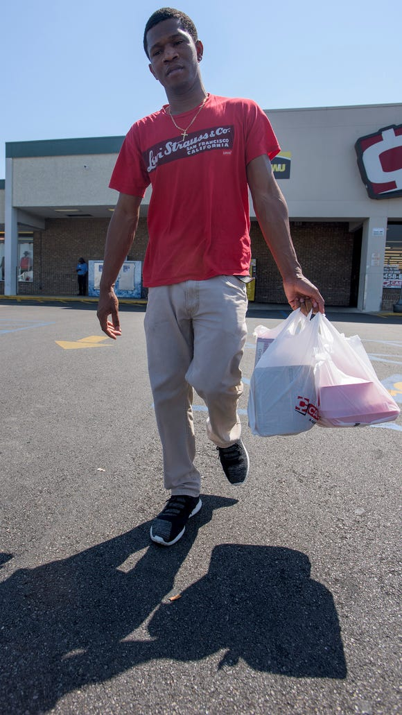 Timothy Williams carries his groceries to his car in
