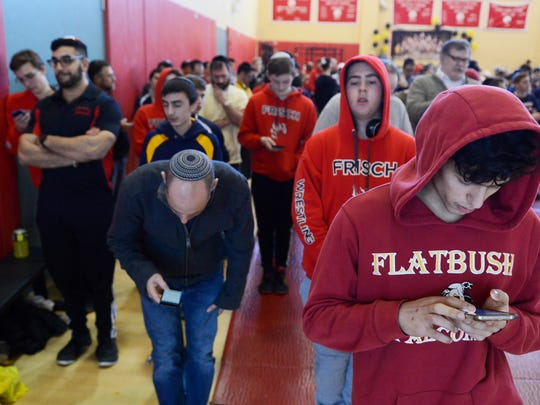 Wrestlers, coaches and spectators participate in a prayer service during the 2017 Wittenberg wrestling tournament on Sunday. Yeshiva high schools from all over the nation competed in the tournament.