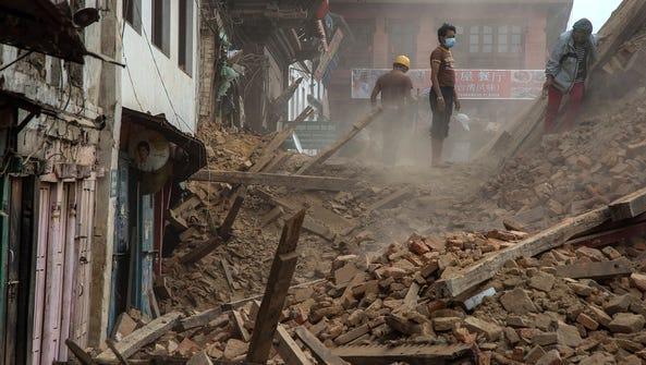 Volunteers and quake emergency team members clear debris