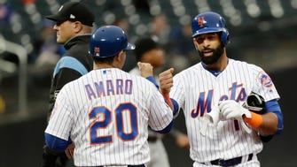 New York Mets' Jose Bautista, right, celebrates with first base coach Ruben Amaro Jr (20) after hitting a double during the second inning of a baseball game against the Miami Marlins Tuesday, May 22, 2018, in New York.
