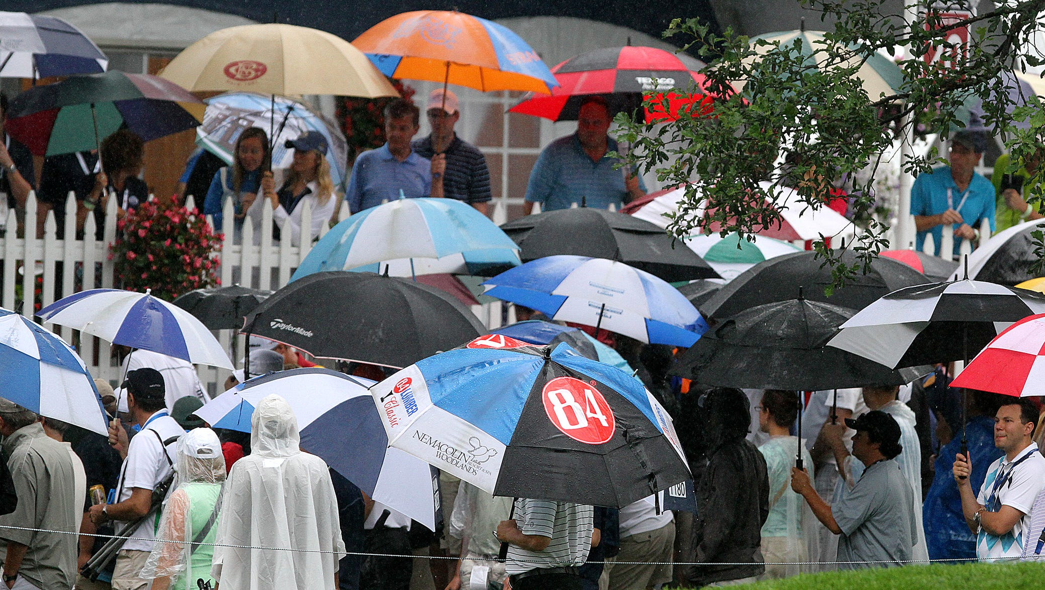 Spectators line the course in umbrellas Friday.