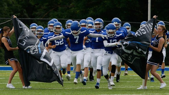 Grove City Christian, led by Josiah Bever (7), takes the field before playing Worthington Christian on Aug. 28.