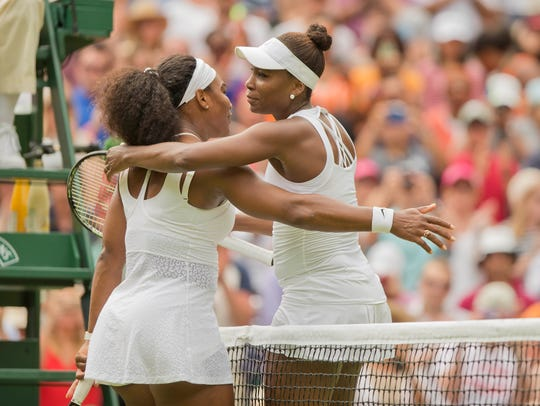 Serena Williams and Venus Williams hug at the net after