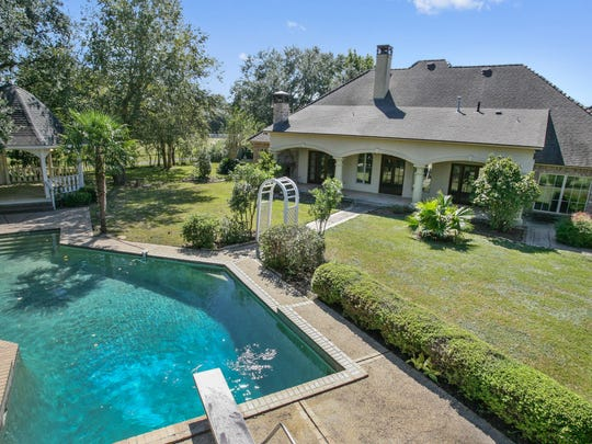 The landscaped yard includes a gorgeous pool and spa.