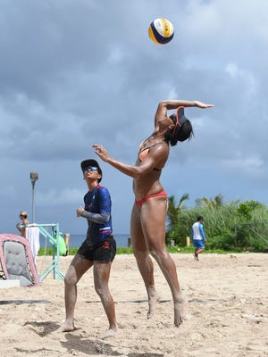 Tatiana Sablan leaps to spike the ball during the Liberation Day Beach Volleyball Open at The Beach Bar and Grill on July 23, 2017.