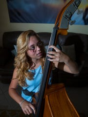 Nichelle Agosto practices on her new bass she received from a high-school student who started a program called Instruments of Hope. Agosto had to leave her bass and country behind because of Hurricane Maria.