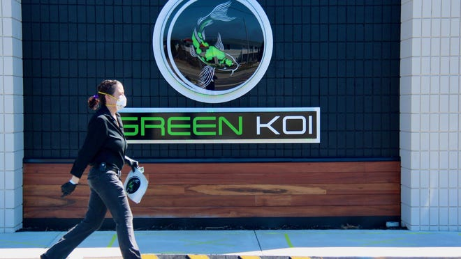 Rachel McCartney with Green Koi delivers an order to a customer on Thursday, April 2. With recreational marijuana introduced locally, the industry is becoming more of an influence in the state's economy.