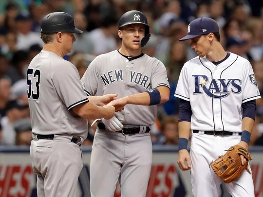 New York Yankees third base coach Phil Nevin (53) looks at the hand of Brandon Drury as Tampa Bay Rays third baseman Matt Duffy looks on during the fifth inning of a baseball game Tuesday, July 24, 2018, in St. Petersburg, Fla. Drury was removed from the game.
