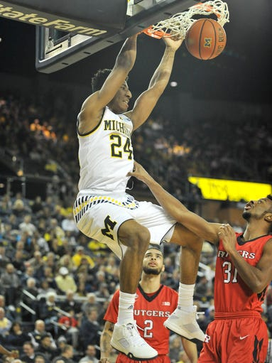 Michigan guard Aubrey Dawkins (24) dunks over Rutgers