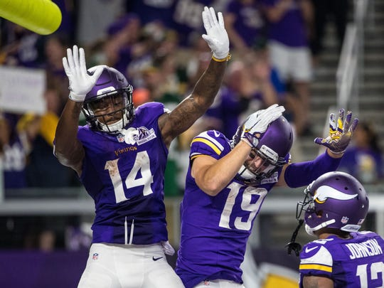 Vikings receiver Stefon Diggs (14) celebrates his touchdown catch with Adam Thielen (19) during the second half against the Packers.