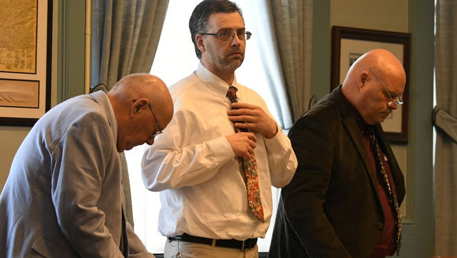 Flanked by his legal team of Robert Whitney and Rolf Whitney, accused killer Shawn Grate straightens his tie during a break in the testimony in his murder trial Thursday afternoon in Ashland County Common Pleas Court.