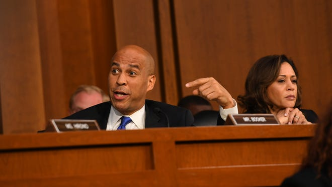 Sen. Cory Booker, D-New Jersey, left, speaks while Sen. Kamala Harris, D-California, listens during the hearing for Supreme Court Associate Justice Brett Kavanaugh before the Senate Judiciary Committee during his confirmation hearing on Sept. 4, 2018. The two senators are among Democrats who've said they're running for president in 2020.