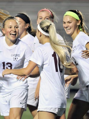 Caravel's Macie Pennington is swarmed on by her teammates after she scored a goal in the first half against Tower Hill.