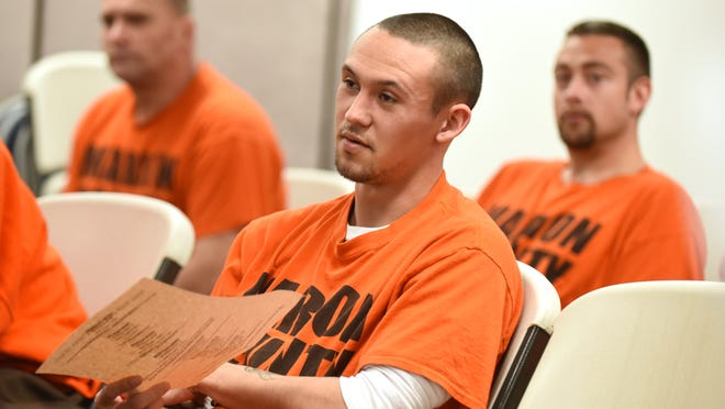 Inmate Johnathan Puckett (center), who is an aspiring tattoo artist, asks questions during a community opportunities panel on April 2 at the De Muniz Resource Center in Salem. Puckett was particularly interested in Salem Art Association's art education opportunities.