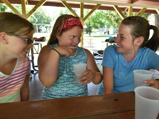Pamela Prescott, from left, Jacqueline Barlas and Emma Stueber compared chocolate milk mustaches during a free public lunch program sponsored by the YMCA at Otumba Park.