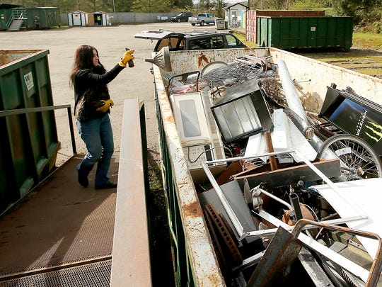 Michelle Kelly, of Poulsbo, tosses scrap metal into
