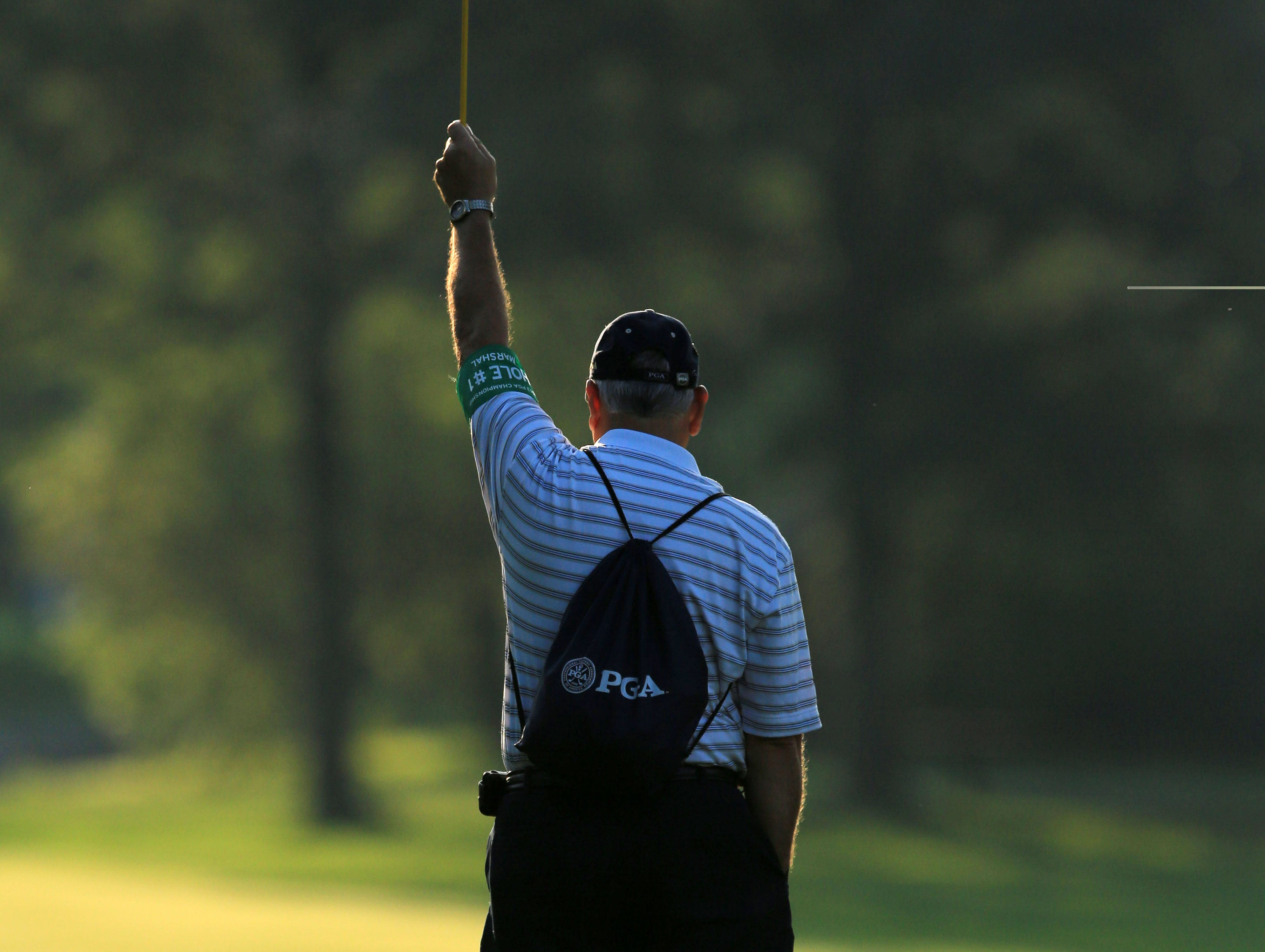 A marshall holds up a flag during the practice round of the 95th PGA Championship at Oak Hill Country Club.