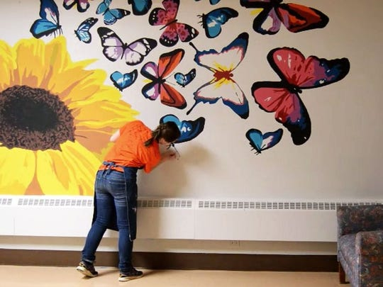 Silver Lake College of the Holy Family student Kaye Solander paints a mural at Sunny Ridge Rehabilitation Center in Sheboygan.