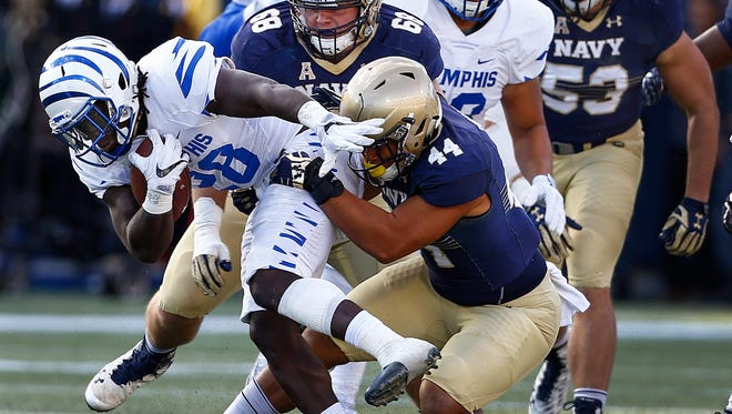University of Memphis running back Doroland Dorceus (left) scrambles past Navy defenders Patrick Forrestal (top) and Micah Thomas (right) during second quarter action at Navy-Marine Corps Memorial Stadium in Annapolis, Maryland.