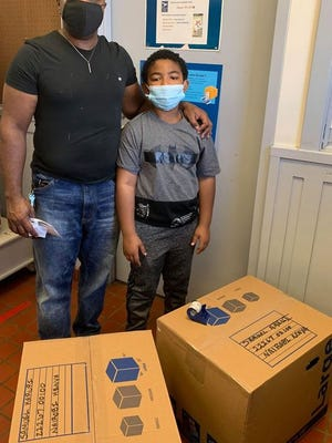 TJ Coleman (left) president of the Aubrey Stewart Project and Little Dude Zavon Evans are shown as they prepare to mail soccer supplies collected for children in Kenya.  Photos courtesy of the Aubrey Stewart Project