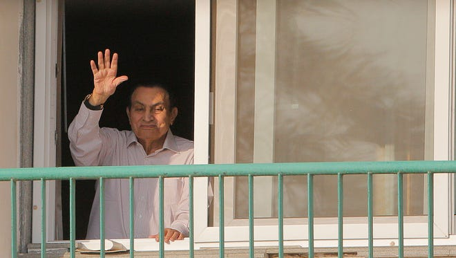 FILE - In this Oct. 16, 1016 file photo, ousted Egyptian President Hosni Mubarak waves to his supporters from his room at the Maadi Military Hospital as they celebrate the 43rd anniversary of the Oct. 6, 1973 war. An Egyptian security official said Froday, March 24, 2017 that the country's ousted President Hosni Mubarak returned home, after his release. (AP Photo/Amr Nabil, File)