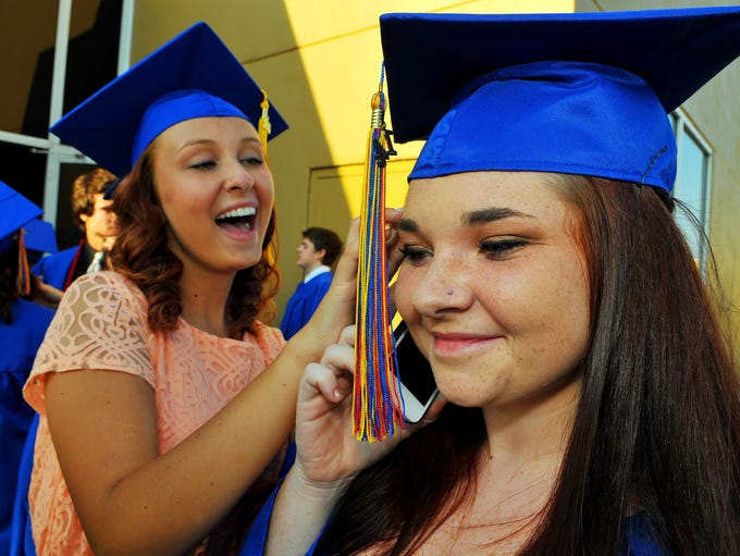 Payton Gripp helps Danielle Curiale get ready for Eau Gallie High School's graduation ceremony on Thursday, May 22, 2014 at the King Center in Melbourne.