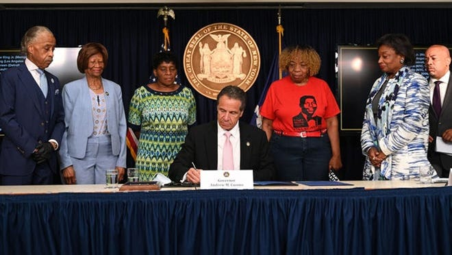 Gov. Andrew Cuomo Friday signs into law a package of police reforms in New York.
