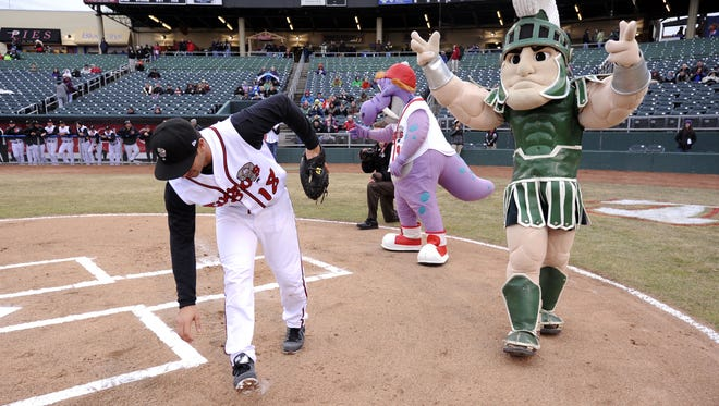 Mascots Big Lug and Sparty react as Lansing Lugnuts catcher Jorge Saez chases down one of the very wild ceremonial first pitches at the Crosstown Showdown in 2014. The Lugnuts and Spartans will compete in their annual exhibition contest tonight.