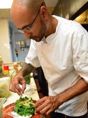 Chef Junior Chamon plates a dish at Graze Restaurant