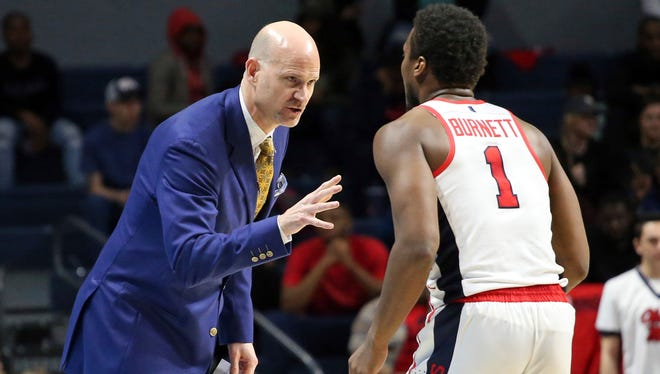 Mississippi coach Andy Kennedy speaks with guard Deandre Burnett (1) during Ole Miss' 75-64 loss to Arkansas.