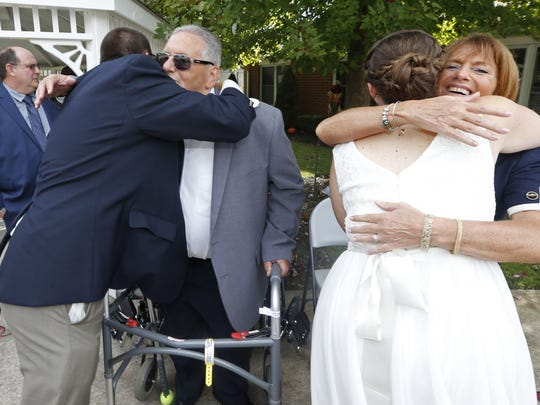 Tom DiPaolo and Ellen Tyndell hug the groom's parents,