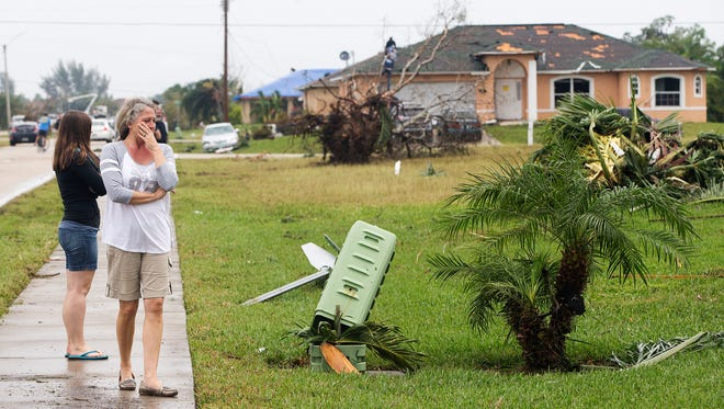 Cape Coral residents take in the aftermath Sunday of the tornado that ripped through Cape Coral late Saturday.