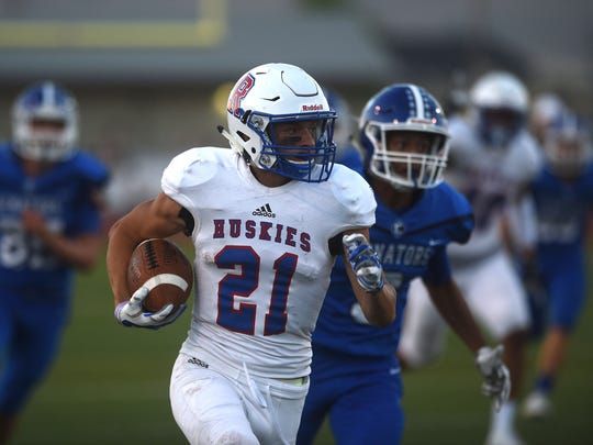 Reno's Evan Moore (21) runs for a first half touchdown while taking on Carson.