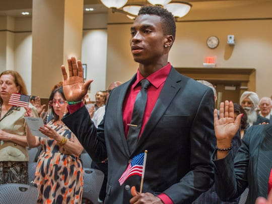 Michigan wide receiver Amara Darboh, left, becomes a U.S. citizen Thursday, Sept. 24, 2015, in Detroit.