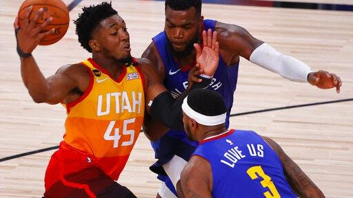 Donovan Mitchell, left, of the Utah Jazz drives against Paul Millsap, center, and Torrey Craig of the Denver Nuggets  during the  fourth quarter of Game Four of the Western Conference first round NBA  playoffs at AdventHealth Arena at ESPN Wide World Of Sports Complex on Sunday.