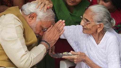 "90-year-old Hiraben blesses her son and India's next prime minister Narendra Modi at her home in Gandhinagar, in the western Indian state of Gujarat, Friday, May 16, 2014. The top official in Gujarat state for over a decade, Modi often contrasted his humble roots with the posh background of his main rival, 43-year-old Rahul Gandhi, heir to India's most powerful political dynasty. As the career politician led his party through a dazzling, high-tech election campaign, Modi called voters' attention to his mother riding a three-wheeled auto-rickshaw to cast her ballot earlier this month. ""I am the chief minister of a prosperous state ... And my 90-year-old mother goes to vote in an auto-rickshaw,"" the white-bearded Modi boasted, punching a fist through the air as he claimed his place by India's poor masses."