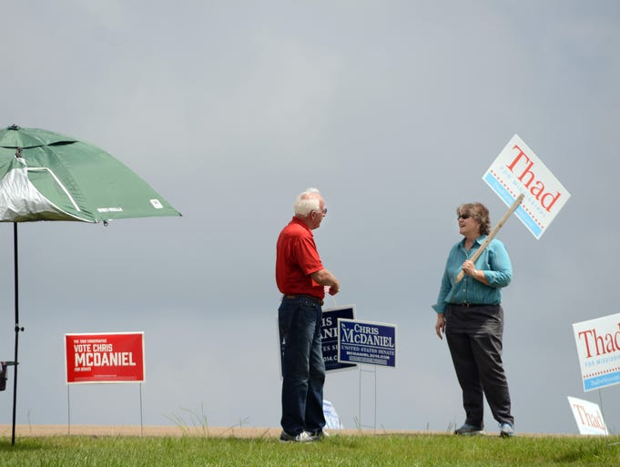 Supporters of U.S. Sen. Thad Cochran and challenger, state Sen. Chris McDaniel, chat while campaigning near the voting precinct located at the Vinyard Church on Mississippi 25 in Flowood on Tuesday.