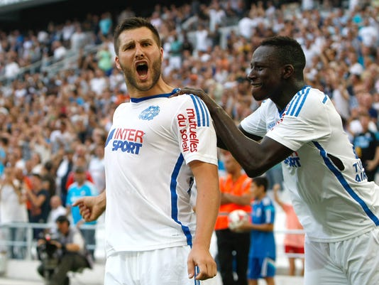 Marseille's French forward Andre-Pierre Gignac, left, reacts with Marseille's French defender Benjamin Mendy, after scoring against Rennes, during their League One soccer match, at the Velodrome Stadium, in Marseille, southern France, Saturday, Sept. 20, 2014. (AP Photo/Claude Paris)