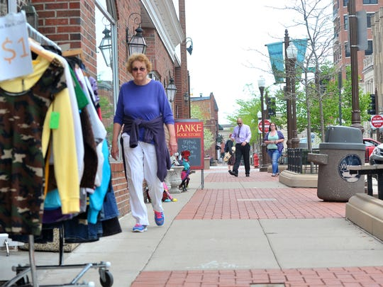 Shoppers walk along Wednesday afternoon on Third Street