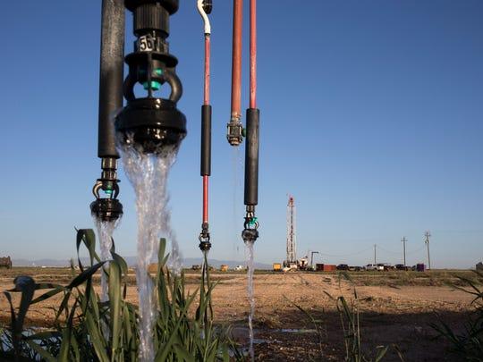 A center pivot irrigates a field while a new 1,200-foot
