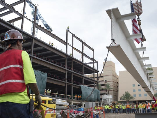 The top beam is lifted into place on Sandra Day O'Connor College of Law in downtown Phoenix. Construction finished in summer 2016.
