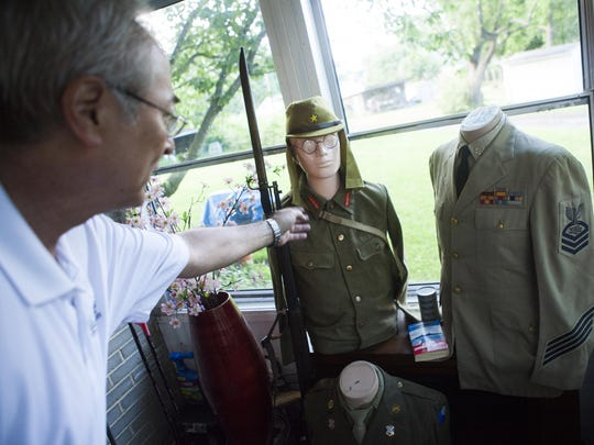 James Belcher Jr. talks about the details of a Japanese military uniform sitting beside his father's Navy uniform, from when he served as a chief petty officer, at his mother's house in Waynesboro on Friday, July 10, 2015.