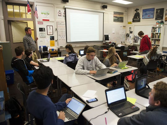 Asheville High School teacher Will Smith, left, discusses upcoming class work with students in his class recently.