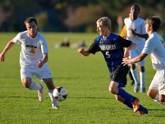 St. Cloud Cathedral's Jake Minkkinen (5) drives the ball between Sauk Rapids' Jeremy Pflipsen (4) and another defender in the first half of their game Monday, Oct. 3, at Sauk Rapids-Rice High School.