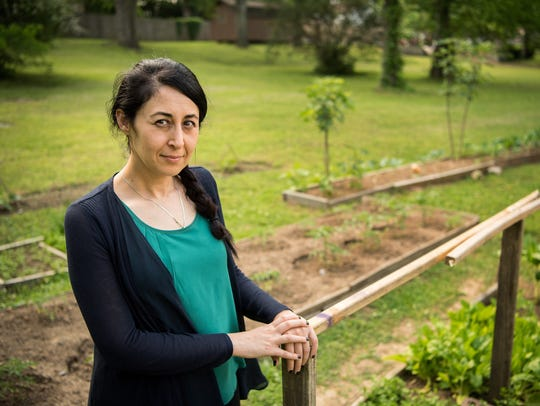 Chimen Mayi stands in the garden at her Nashville home