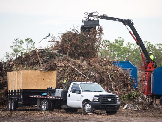 Workers remove Hurricane Irma debris from trucks at a collection site on Wiggins Pass Road in North Naples on Sept. 27, 2017.