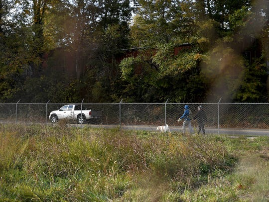 A pair walks a dog down the sidewalk along the fence