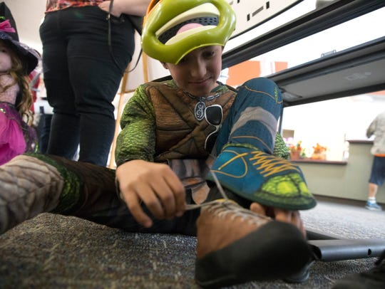 Edwardo Montoya laces up his shoes before competing in the annual Boo-ouldering Competition Monday afternoon at the climbing wall at San Juan College Health and Human Performance Center in Farmington.